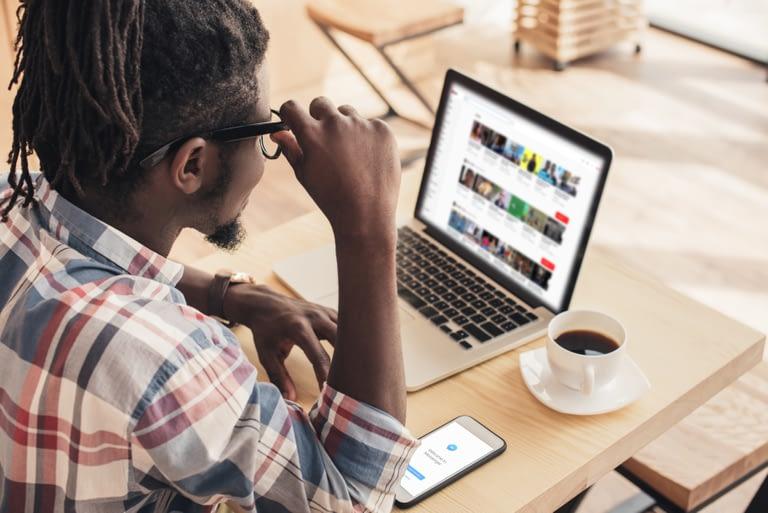 Man browsing YouTube on laptop